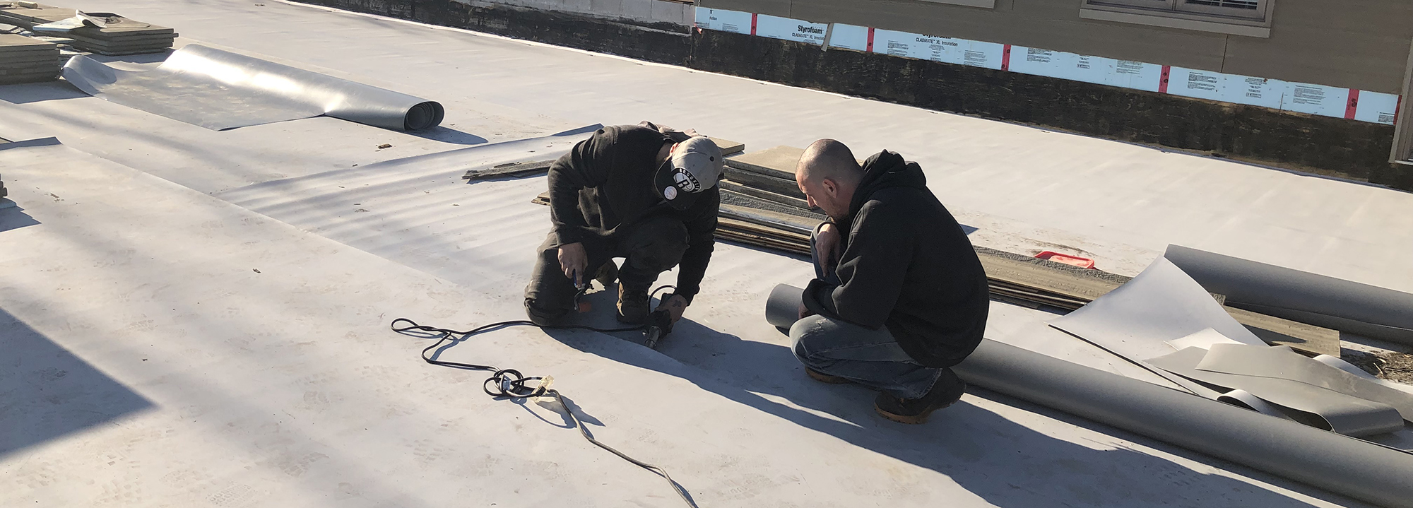 Workers install a TPA flat roof.